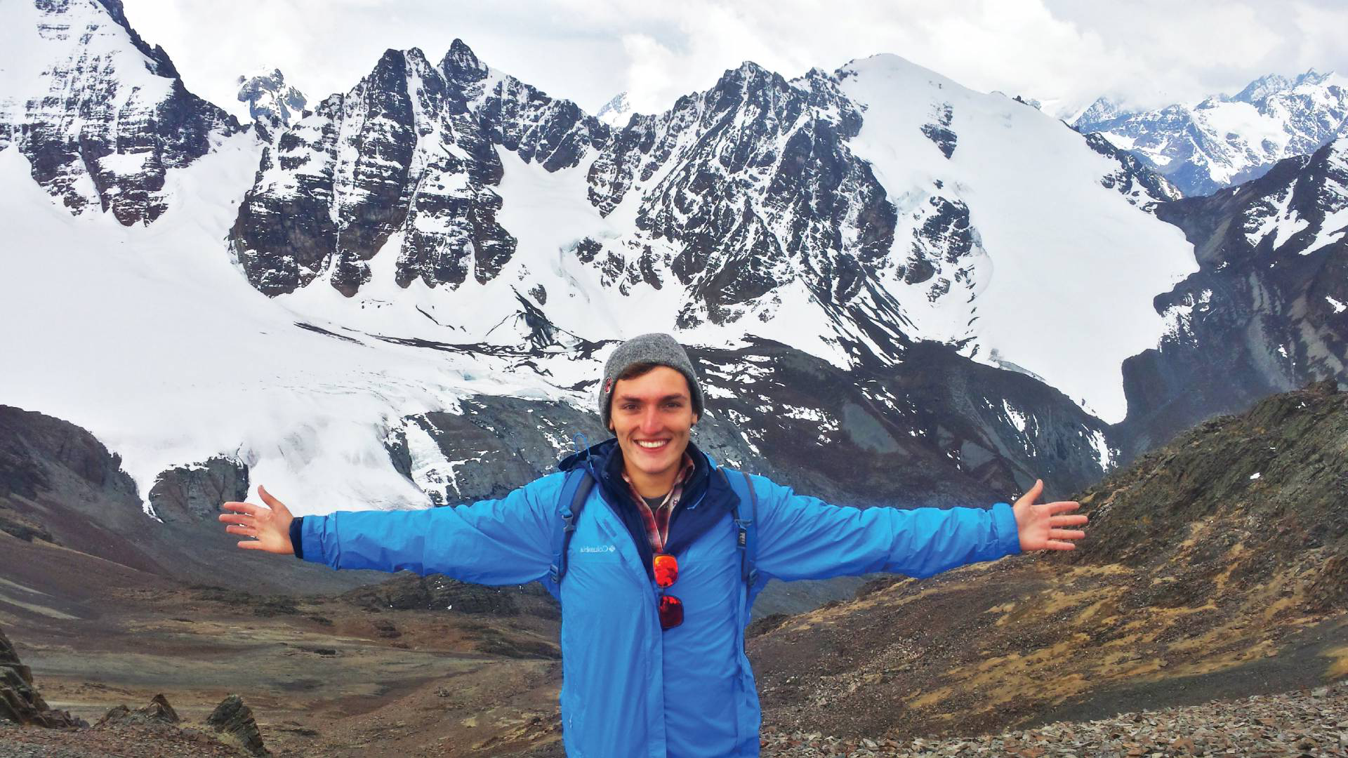Bridge Year student stands in front of a snowy mountain range, arms spread wide