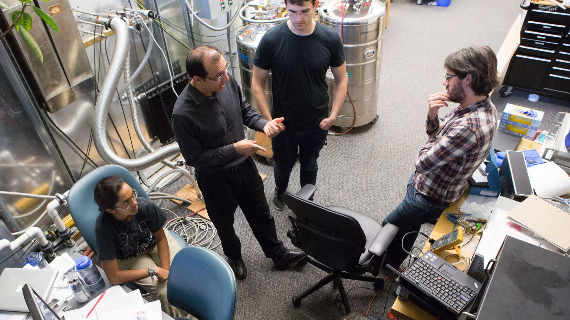 Professor and students confer in a lab.