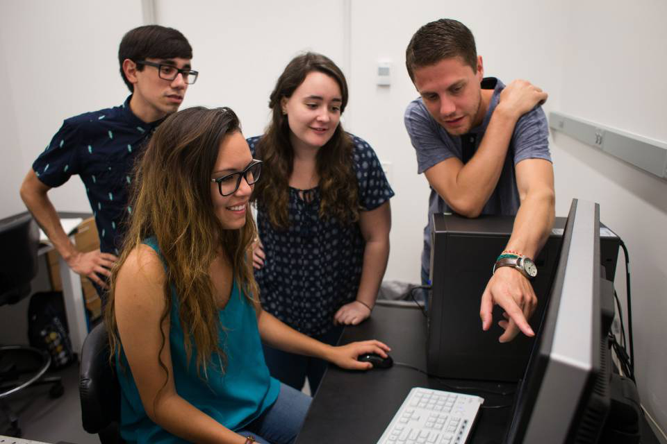 Graduate students gather around a computer while one student points at the screen