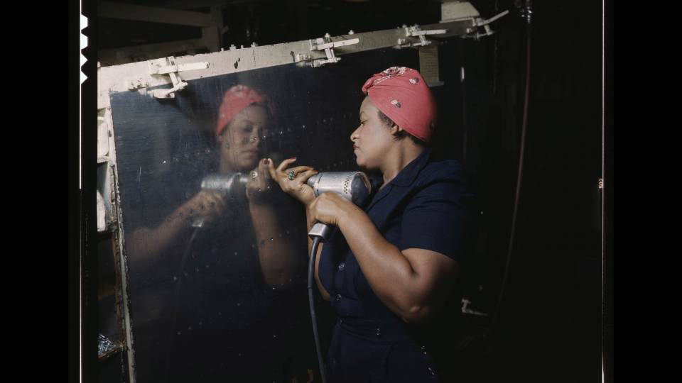 A woman installs rivets in the wartime labor effort