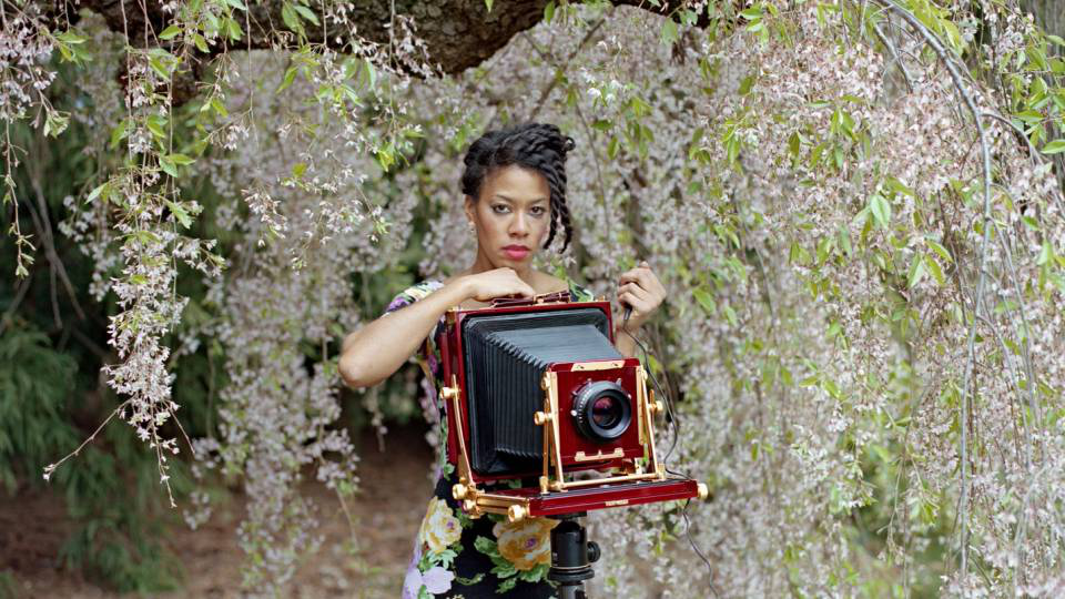 Deana Lawson behind a square-format camera amongst cherry blossoms