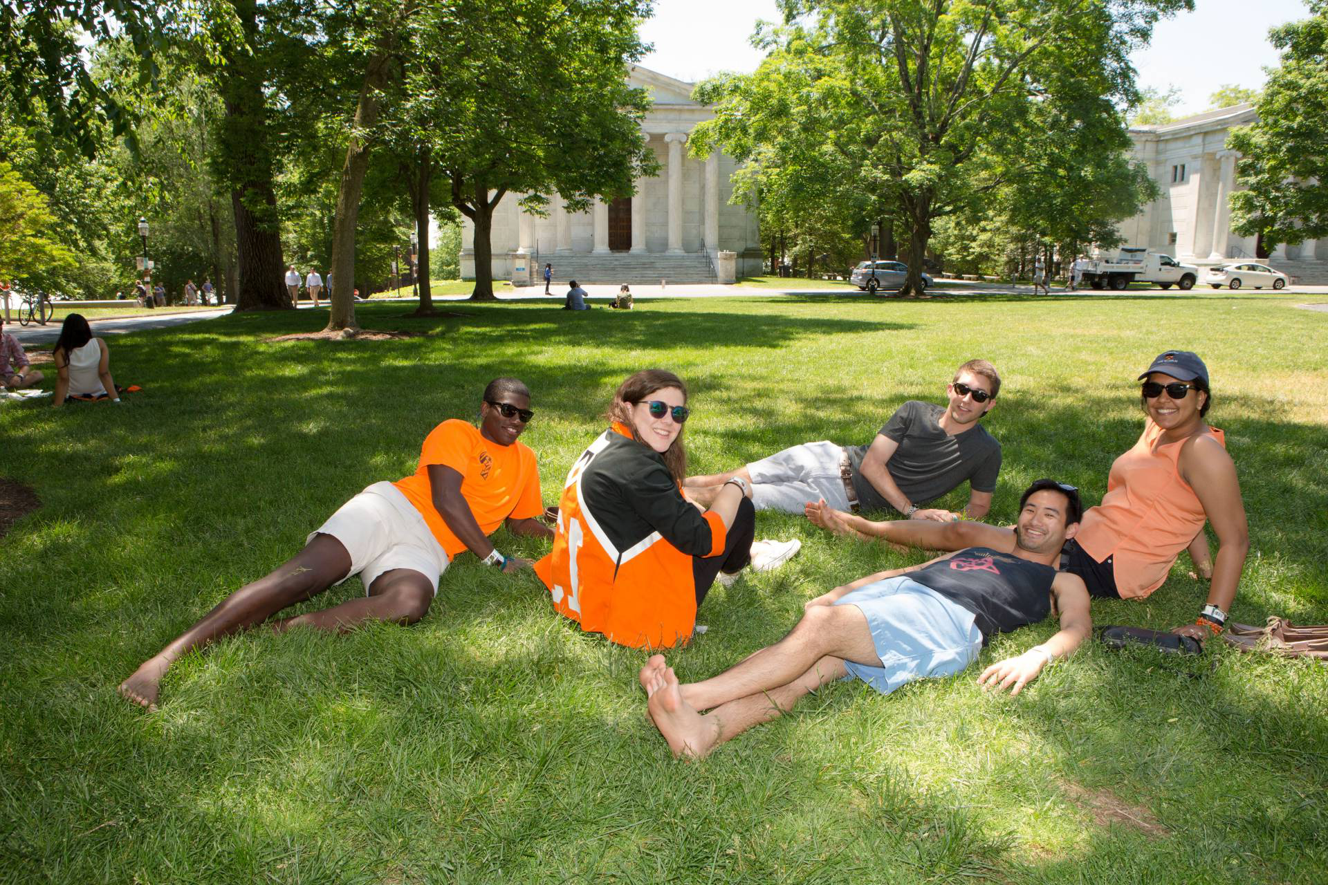 Photo of alumni lying on grass on Cannon Green.