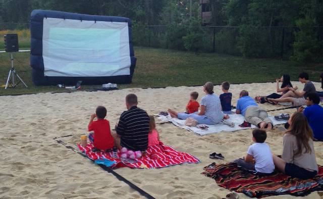 Graduate students with families watching a movie outdoors